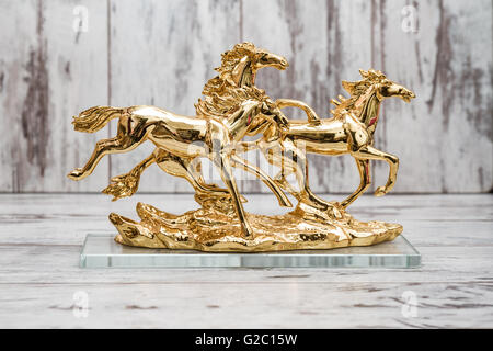 Statuettes of golden horses on white wooden background - Stock Photo