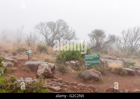 A warning sign and route marker in thick fog on the Crag Lizard trail near the Valley of Desolation viewpoint - Stock Photo