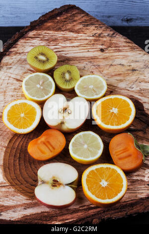 Slices of various fruits on freshly cut wooden stump. Kiwi, orange, apple, lemon, and persimmon - Stock Photo