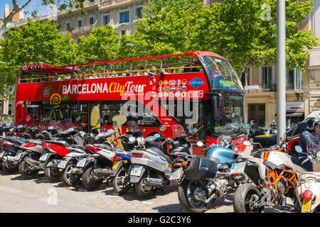 Spain Catalonia Barcelona Eixample Passeig de Gracia City Tourist Bus red double decker open top by motor bike cycle - Stock Photo