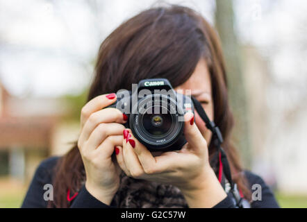 Young woman taking pictures at the park - Stock Photo
