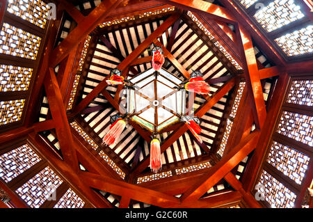Chinese lantern hanging from wooden beams in the ceiling of an Oriental Gazebo - Stock Photo