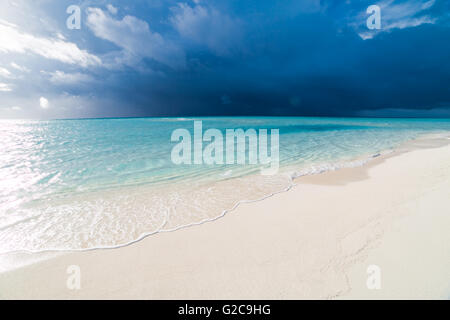 White tropical beach in Maldives with blue lagoon and a tropical storm - Stock Photo