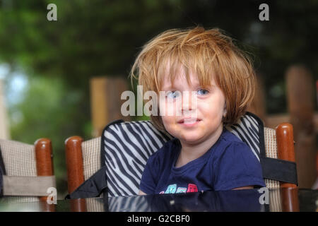 Disheveled and dirty girl punished on a chair in a summer school - Stock Photo