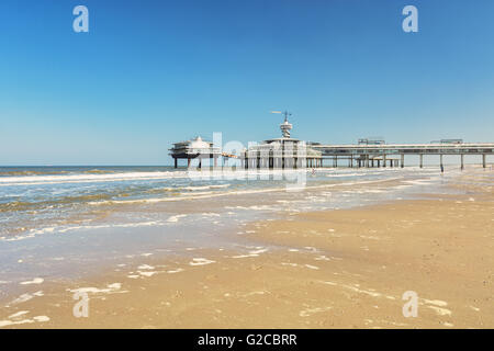 View from the beach to the pier with bungee jumping in Scheveningen, Netherlands. - Stock Photo