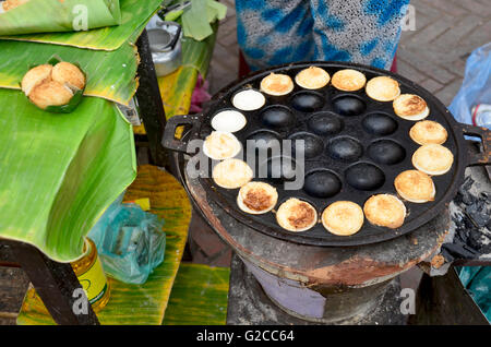 Cooking Thai Dessert : Coconut milk custard in small porcelain cup or Coconut-rice pancakes called Kanom krok - Stock Photo