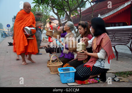 Tradition of almsgiving with sticky rice by Monks procession walk on the road for people put food offerings at Wat - Stock Photo