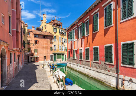 Narrow street and oats on canal between colorful houses under blue sky in Venice, Italy. - Stock Photo