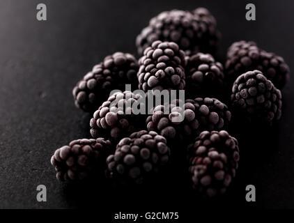 blackberries frozen on a black stone, macro photo showing a beautiful ice texture - Stock Photo