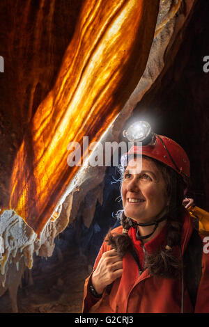 Female caver with curtain formation in cave Grotta Impossibile, Italy - Stock Photo