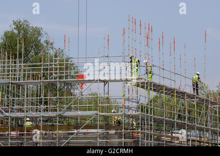 Workmen walking along Scaffolding on a new building - Stock Photo