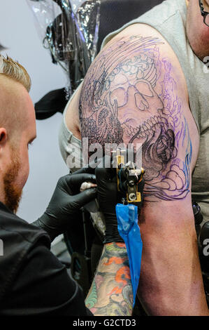 BELFAST, NORTHERN IRELAND. 28 MAY 2016 - 6th Northern Ireland Tattoo Conference. A tattoo artist draws a tattoo - Stock Photo