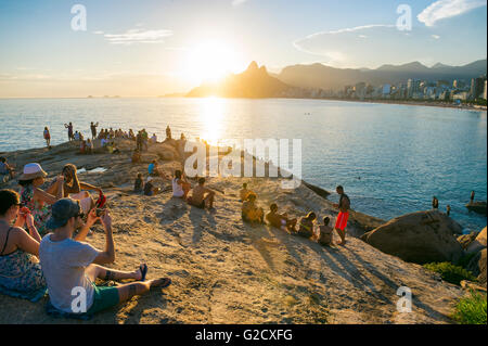 RIO DE JANEIRO - FEBRUARY 26, 2016: Crowds of people gather to watch the sunset on the rocks at Arpoador. - Stock Photo