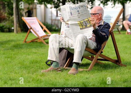 Hay Festival - Friday 27th May 2016 - A festival visitor enjoys the chance to sit down and read the newspaper as - Stock Photo