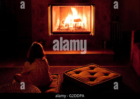 Girl Sitting on Floor Near Fireplace, Rear View - Stock Photo