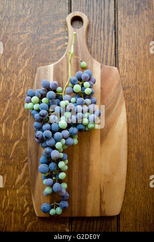 Wild Grapes on Wooden Cutting Board - Stock Photo