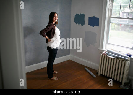 Pregnant Woman Decorating Nursery - Stock Photo