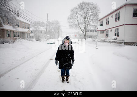 Young Adult Woman Woman Walking Down Middle of Snowy Street During Storm - Stock Photo