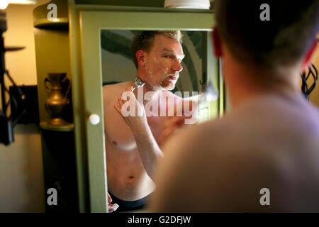 Man Shaving in Mirror - Stock Photo