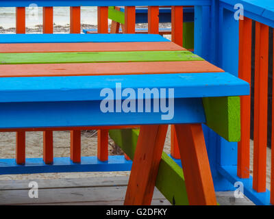 blue, red and green painted railing and painted wooden picnic table sitting on a deck in Turks and Caicos - Stock Photo