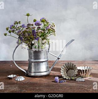 Bouquet of wild flowers in old metal ewer - Stock Photo
