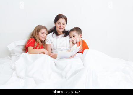 mom reading a book in bed for her child before sleep - Stock Photo