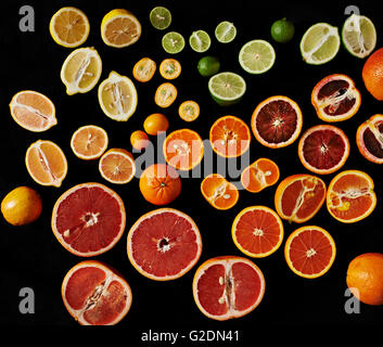 Variety of Sliced and Whole Citrus Fruit on Tray, High Angle View - Stock Photo