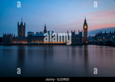 Palace of Westminster in London, and the Big Ben at night with vehicle leaving a trail along the road, with a clear - Stock Photo
