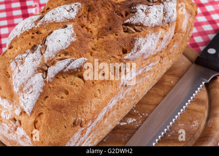 Home made bread closeup on wood plate with cutting knife - Stock Photo