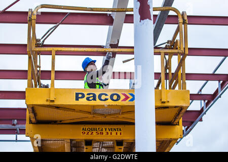 male painter working on a yellow lifting work platform beside a dock in Santa Cruz de Tenerife - Stock Photo