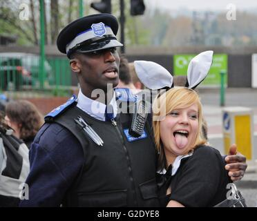 A young girl posses with a traffic warden in Kentish Town, London, after having enjoyed a Sunday afternoon at the - Stock Photo