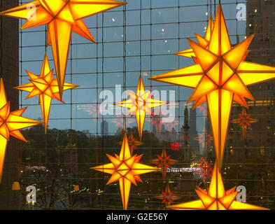 very large hanging Christmas ornaments hanging in the lobby of a building in New York City - Stock Photo