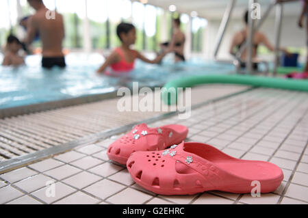 Boeblingen, Germany. 28th May, 2016. Sandals lie by the side of the pool during swimming lessons for refugee children - Stock Photo