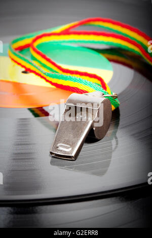silver colored whistle with red, yellow and green striped cord on a vinyl record - Stock Photo
