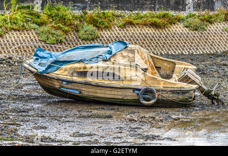 Seemingly abandoned small cabin cruiser lying on the mud at low tide and looking extremely worse for wear - Stock Photo