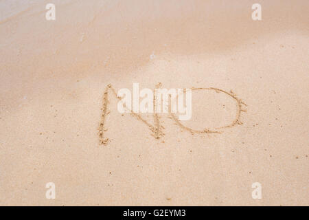NO sign written in sand on beach texture sunny background. Closeup - Stock Photo