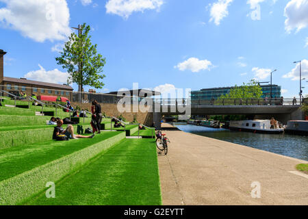 London, UK - May 23, 2017 - People relax and enjoy sunshine on the terrace at Granary Square, King's Cross - Stock Photo