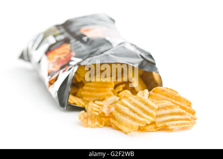 Crinkle cut potato chips isolated on white background. Potato chips poured out from packing. - Stock Photo