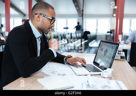 Concentrated young businessman looking at his laptop while sitting at his working place in office - Stock Photo