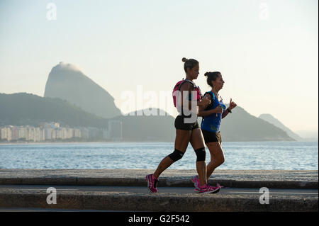 RIO DE JANEIRO - APRIL 3, 2016: A pair of joggers on the Copacabana boardwalk pass in front a Sugarloaf Mountain - Stock Photo