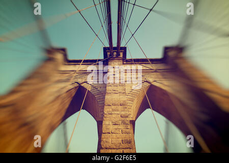 Detail of the stonework of one of the towers on Brooklyn Bridge with a blur vignette obscuring the side suspension - Stock Photo