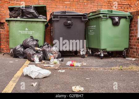 Overflowing commercial dustbins on the street in Hereford, Herefordshire, England, UK - Stock Photo