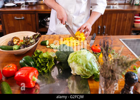 Closeup of chef cook standing and making salad on the kitchen - Stock Photo