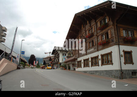 Grindelwald, Switzerland - August 19, 2014: Buildings, bus and unidentified people on street in Grindelwald in Switzerland. - Stock Photo