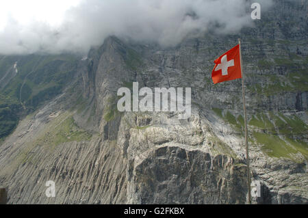 Swiss flag fluttering on wind high in mountains nearby Grindelwald in Alps in Switzerland. - Stock Photo