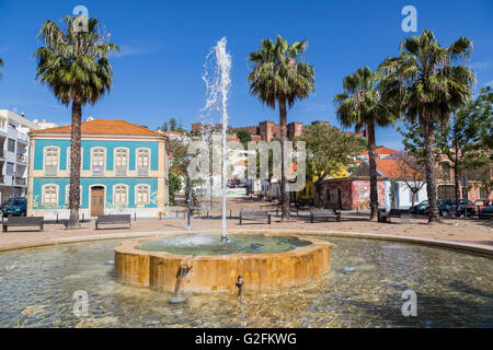 Fountain in public space with castle on skyline, Silves, Algarve, Portugal - Stock Photo