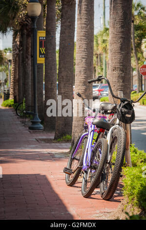 Bicycles parked along a palm tree lined street in front of beachside area restaurants in Atlantic Beach, Florida. - Stock Photo