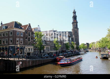 Canal boat on Prinsengracht canal. In background Anne Frank House & historical 17th century Westerkerk, Jordaan - Stock Photo