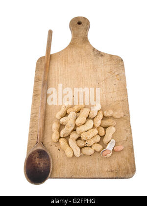 Monkey nuts aka peanuts in shells. Isolated on board with spoon. Forced perspective effect. - Stock Photo