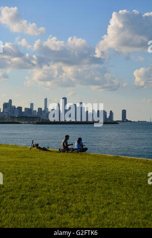 A couple take a break on the lake front park bike trail on the south side of Chicago in the Kenwood neighborhood. - Stock Photo